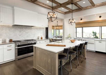 new kitchen with stylish lamps for lighting and an off white island